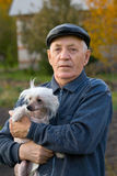 Elderly man with a dog. Portrait of the elderly man with a dog of breed chinese crested against the nature Royalty Free Stock Image