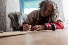 Elderly man doing calligraphy using a nib pen. And ink or pigment from a pot in a low angle tilted view across a wooden table with foreground copy space stock images