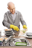 Elderly man doing the dishes Stock Photos