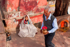 Elderly man with donations going to the temple by poor woman Stock Photography