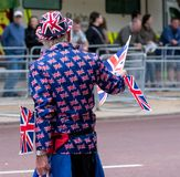 Elderly man dressed in jacket and hat decorated with union jack flags, and waving union jack flags waits for the Trooping of the C royalty free stock photos