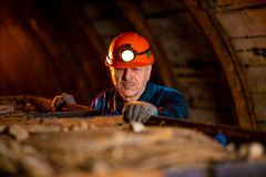 An elderly man dressed in work overalls and a helmet stands near the old inverted vogonetki. Miner royalty free stock image