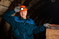 An elderly man dressed in work overalls and a helmet stands near the old inverted vogonetki. Miner stock photography