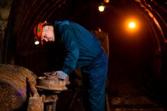 An elderly man dressed in work overalls and a helmet stands near the old inverted vogonetki. Miner stock photos