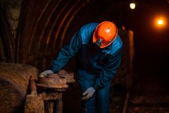 An elderly man dressed in work overalls and a helmet stands near the old inverted vogonetki. Miner stock image