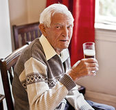 Elderly man with a drink. Cheers, happy elderly man with a drink royalty free stock photography