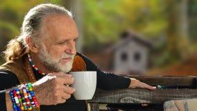 Elderly man drinking coffee Stock Images