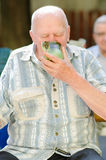 Elderly man drinking Royalty Free Stock Photos