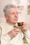 Elderly man drinking cup of coffee Royalty Free Stock Photos