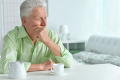 Elderly man drinking cup of coffee Stock Image