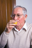 Elderly man drinking Royalty Free Stock Photography