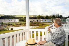 Elderly man drinking a mug of coffee sitting on the veranda of a. Luxury static caravan in North Wales taking in the scenic views of the Welsh Countryside stock photo