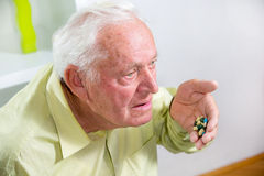 Elderly man drinking pills Stock Image