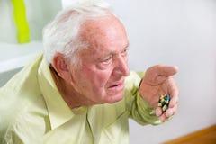 Elderly man drinking pills Stock Image