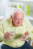 Elderly man drinking pills and water Stock Images
