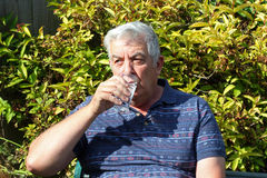 Elderly man drinking water. An elderly man drinking a glass of water Stock Photography