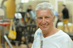 Elderly man drinking water after exercise. Elderly man in a gym. drinking water after exercise stock image