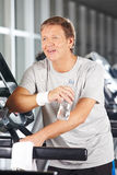 Elderly man drinking water in fitness center Stock Photography