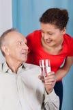Elderly man drinking water. Elderly men drinking water and his granddaughter Stock Image