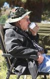 Elderly man drinks coffee. A senior citizen, age 83, drinks a cup of takeout coffee while he sits outside and enjoys the fresh air Stock Photos