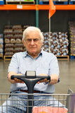 Elderly man drives motorized wheelchair Royalty Free Stock Photography