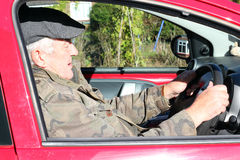 Elderly man driving a car. An elderly man with his hands on the steering wheel driving a car and looking ahead Royalty Free Stock Image