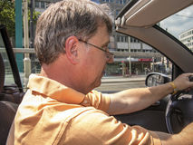 Elderly man driving his cabrio on a sunny day Royalty Free Stock Photos
