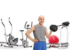 Elderly man with a dumbbell in front of exercise machines. Isolated on white background stock photos