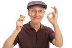 Elderly man eating a cookie royalty free stock photo