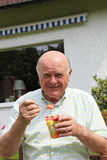 Elderly man eating fresh fruit salad Stock Photo