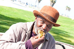 Elderly man eating hotdog Royalty Free Stock Photography