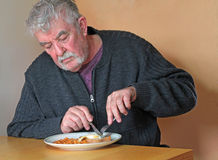 Elderly man eating at a table. stock photos