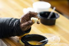 Poor man warm soup. Elderly man eats warm soup with bread in a kitchen with free food for poor and homeless people stock images
