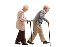 Elderly man and an elderly woman with canes walking. Full length profile shot of an elderly men and an elderly women with canes walking isolated on white Royalty Free Stock Photos