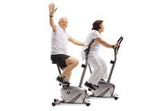 Elderly man and an elderly woman riding exercise bikes with the Royalty Free Stock Images