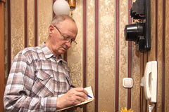 An elderly man electric meter. Readings Royalty Free Stock Images