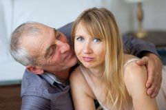 Elderly Man is Embracing and Kissing his Young Wife in Sexy Lingerie Lying in Bed in Their Home. Couple with Age. Elderly Man Embracing and Kissing his Young Royalty Free Stock Photography