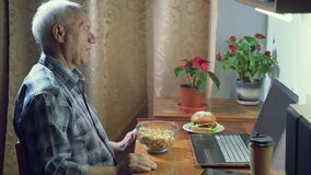 An elderly man emotionally rooting for his favorite team watching a sports game on a laptop at home