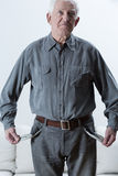 Elderly man with empty pockets Stock Images