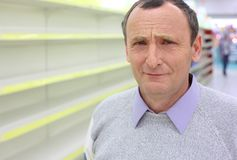 Elderly man and empty shelves Royalty Free Stock Photography