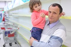 Elderly man at empty shelves in shop with child stock photo