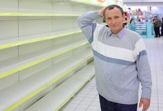 Elderly man at empty shelves in shop scratches Stock Photography