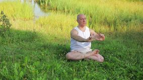 An elderly man is engaged in meditation on the lake in the morning. Overall plan stock video