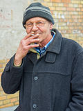 Elderly man enjoying a cigarette outside Stock Photo