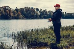 Elderly man enjoys fishing by the river. In the summer. River pike fishing  background royalty free stock images