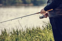 Elderly man enjoys fishing by the river. In the summer. River pike fishing  background stock images