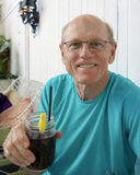 Elderly man enjoys a soda. An elderly sixty-nine year-old man enjoys a soda in a restaurant.  The soda is in a jar he is holding in his right hand and it has a Stock Images