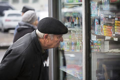 Elderly man examines a shop window royalty free stock image