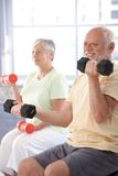 Elderly man exercising with dumbbells Stock Photos