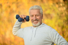 Elderly man exercising with dumbbells. In autumn park royalty free stock images